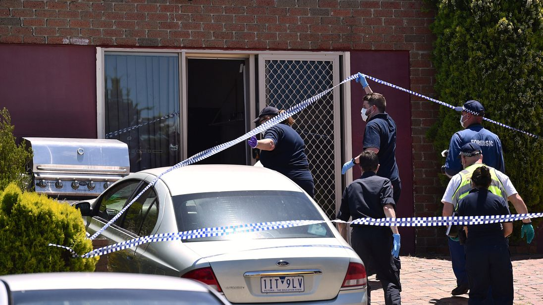 Police walk towards a door as they search a house in the Melbourne suburb of Meadow Heights