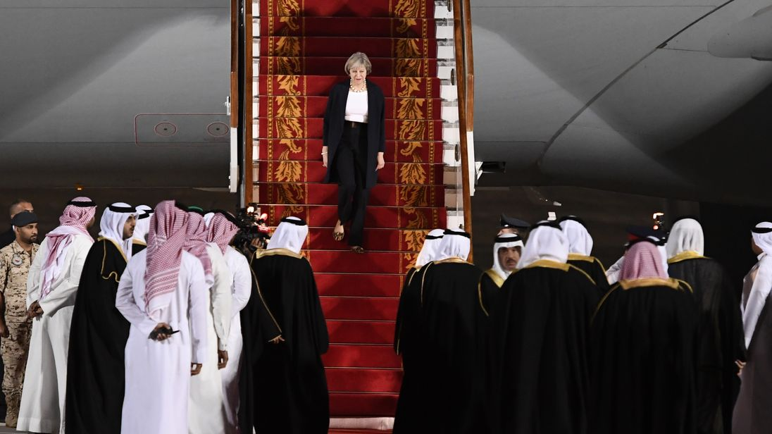 Theresa May steps off a plane in Manama, Bahrain