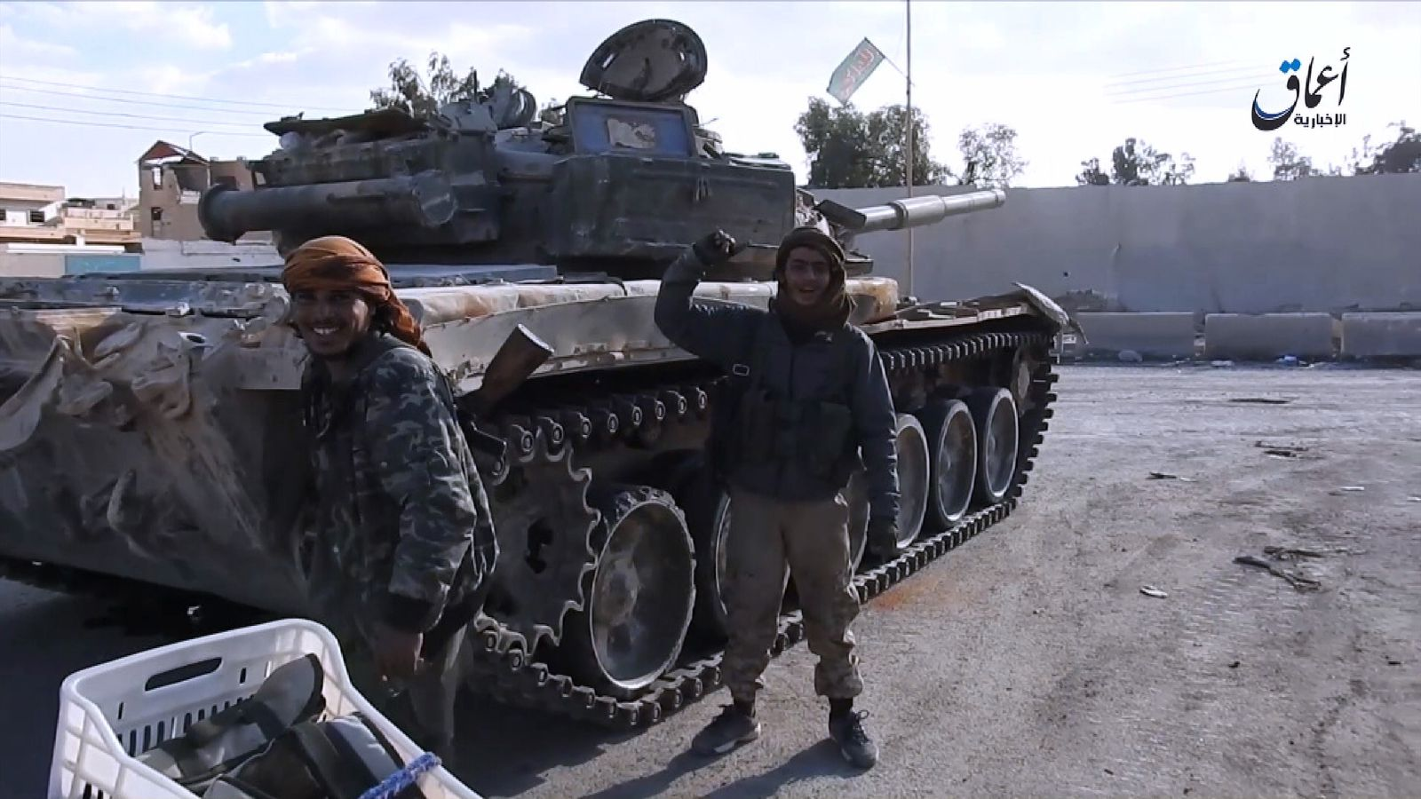 IS fighters with what they say are military vehicles captured in Palmyra