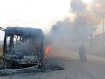 A bus burning as it made its way to evacuate people from besieged cities