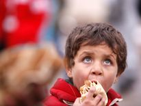 A Syrian boy evacuated from eastern Aleppo, eats bread in government controlled Jibreen area in Aleppo, Syria November 30, 2016. REUTERS/Omar Sanadiki