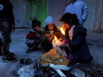 Syrians evacuated from eastern Aleppo, light a fire using plastic bags to keep warm, inside a shelter in government controlled Jibreen area in Aleppo, Syria November 30, 2016. REUTERS/Omar Sanadiki