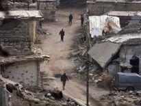 Syrian pro-government troops walk on a street in Aleppo's eastern Karm al Jabal neighborhood