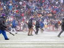 Stadium workers in Orchard Park, NY, trying to clear the field of snow Credit: Kevin Hoffman-USA TODAY Sports