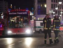 Firefighters walk near the site where a truck speeded into a christmas market in Berlin, on December 19, 2016 killing nine persons and injuring at least 50 people.