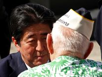 Japanese Prime Minister Shinzo Abe speaks with a Pearl Harbor survivor after he and U.S. President Barack Obama spoke at Joint Base Pearl Harbor-Hickam, Hawaii, U.S., December 27, 2016