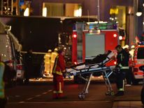 Medics carry an injured person in front of a truck that crashed into a christmas market at Gedächniskirche church in Berlin