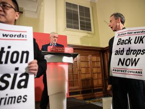 Jeremy Corbyn exchange a glance during a protest at the Labour leader's speech