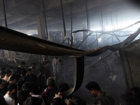 Pakistan rescue workers and people gather in a garment factory following a fire in which at least 289 people died in Karachi on September 13, 2012, on the third day of the fire incident. Police in Karachi have registered a murder case against the owners of a garment factory where a fire killed at least 289 people in the country's worst ever industrial disaster, officers said