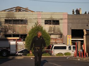 Firefighters and police at the scene of a overnight fire that claimed the lives of at least nine people at a warehouse in the Fruitvale neighborhood on December 3, 2016 in Oakland, California