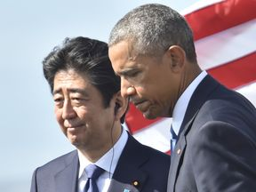 US President Barack Obama (R) walks with Japanese Prime Minister Shinzo Abe after they spoke on Kilo pier near the USS Arizona Memorial December 27, 2016 at Pearl Harbor in Honolulu, Hawaii