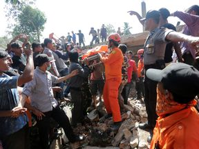 Rescue workers and police remove a victim from a collapsed building following an earthquake in Lueng Putu, Pidie Jaya in the northern province of Aceh, Indonesia December 7, 2016. Pic: Antara Foto/ Irwansyah Putra