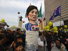 Protesters carry an effigy of South Korea's President Park Geun-Hye