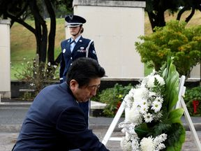 Japanese Prime Minister Shinzo Abe presents a wreath at the National Memorial Cemetery of the Pacific at Punchbowl in Honolulu, Hawaii