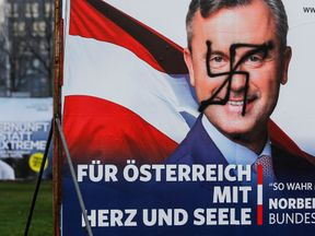 A vandalised poster of Norbert Hofer is seen next to a poster of rival Alexander Van der Bellen