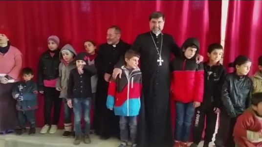 Syrian Bishop Mar Afram Athneil with some of the Assyrian Christian children rescued from Islamic State