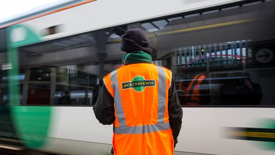 A Southern rail conductor looks on as a Southern rail train leaves East Croydon station on October 18, 2016 in London, England