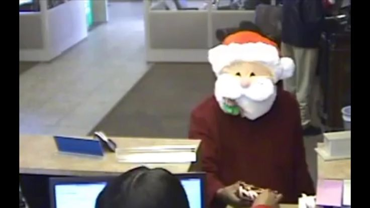 The robber wearing a Santa mask as he demands money from a bank in Memphis. Pic: Memphis Police/Facebook via Storyful