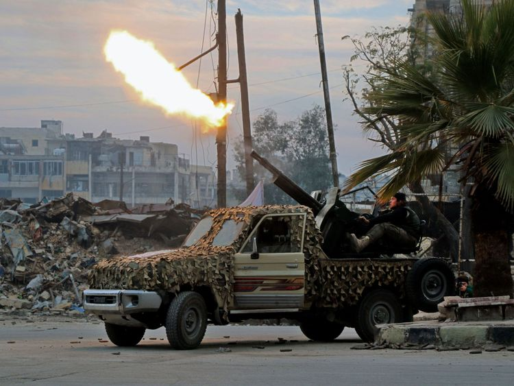 Fighters of the Free Syrian Army fire an anti-aircraft weapon
