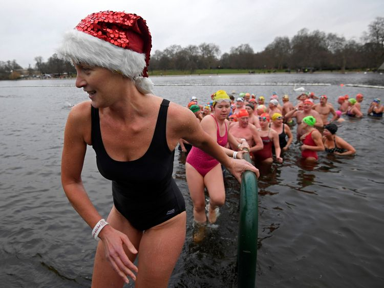 Swimmers take part in the annual Christmas Day race in the Serpentine lake in Hyde Park, London