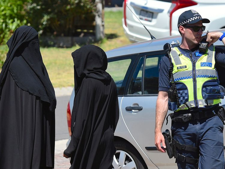 Two women stand next to a policeman blocking a road where police officers are searching a house in the Melbourne suburb of Meadow Heights