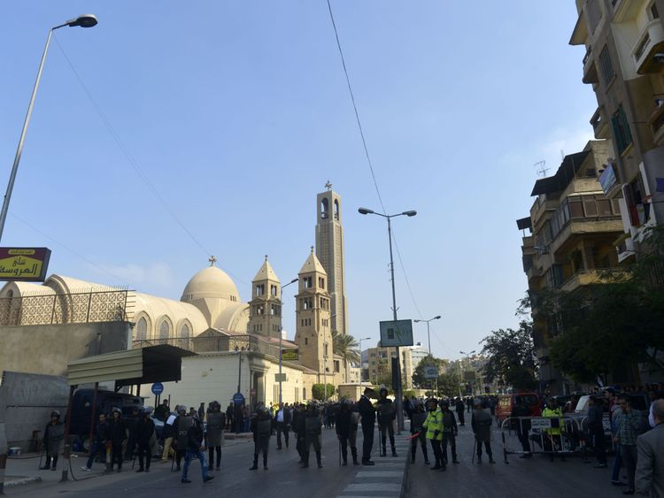 Police and onlookers after the blast at the Coptic cathedral in Cairo