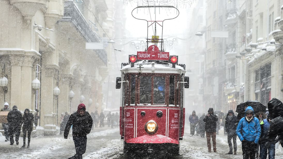 A tram makes its way down a snowy Istiklal Avenue in Istanbul