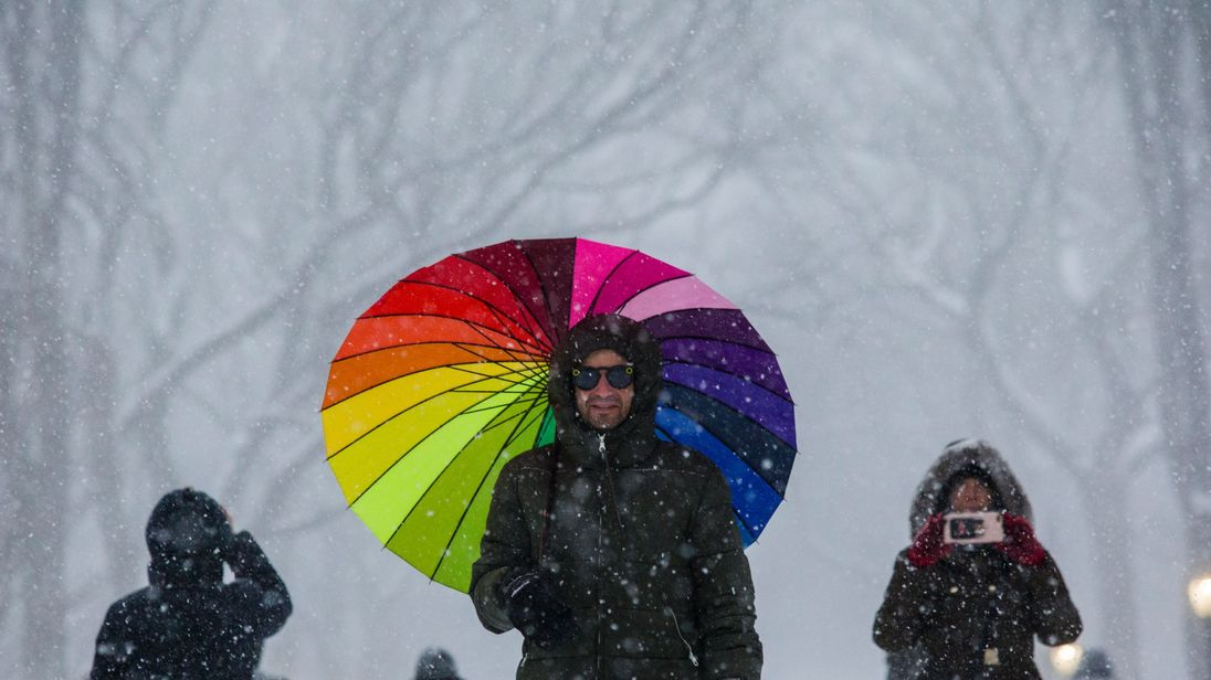 People walk under a snowfall as they visit Central Park during a winter storm on January 7, 2017 in New York