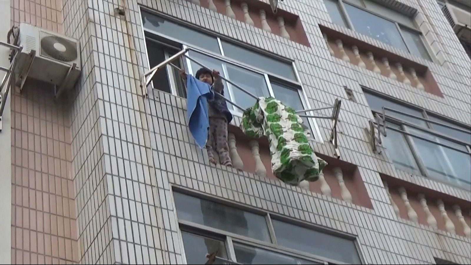 A five-year-old girl who fell from a fourth floor of a building in Qingdao, China, was rescued by firefighters after getting caught by a laundry rack
