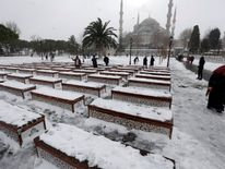 People stroll at the snow-covered Sultanahmet square in Istanbul