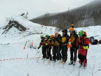 Rescue teams probe the snow in the search for survivors