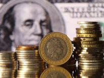 Pound coins are seen in front of a displayed U.S. 100 dollar banknote in this picture illustration 18 Jan 2017