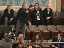 A protester is removed from the gallery at Congress