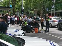 Members of the public watch as police and emergency services attend to an injured person after a car hit pedestrians in central Melbourne, Australia, January 20, 2017
