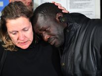 British traveller Sara Wilkins consoles fellow passenger Ebrima Jagne of Gambia after they arrived on repatriation flights organised by tour operator Thomas Cook at Manchester Airport