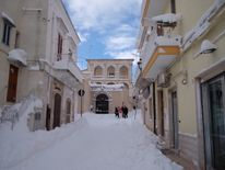 People walk in a street of Santeramo in Colle after snowfalls near Bari in the Puglia region in the south of Italy