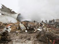 Rescue teams are seen are seen at the crash site of a Turkish cargo jet near Kyrgyzstan's Manas airport outside Bishkek
