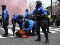 An protester is held to the floor and handcuffed by riot police