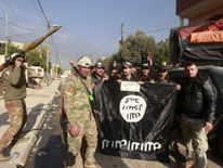 Members of the Iraqi rapid response forces stand with an Islamic State flag which they pulled down during a battle between Iraqi forces and Islamic State militants in the Wahda district of eastern Mosul, Iraq, January 8, 2017