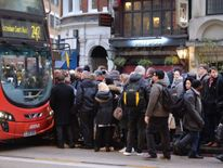 People queue for buses at Liverpool Street station