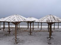 Beach umbrellas are covered with snow at the beach in the town of Artemida in Greece