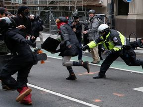 A police officer tries to tackle a protester demonstrating against U.S. President Donald Trump in Washington