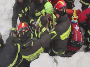Firefighters rescue a survivor who was trapped in the hotel