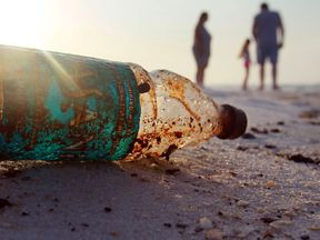 A plastic bottle has travelled miles and washed up on a beach.