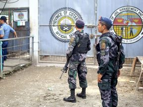 Armed police stand guard at the gates of the district jail
