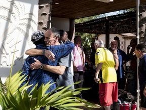 A Tourist embraces a local man as he and other tourists prepare to leave their hotel in Banjul