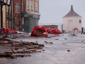 Flood defences and debris litter a street in Whitby after a tidal surge at high tide causes flooding on January 13, 2017 in Whitby, United Kingdom. Strong northerly winds combined with a tidal surge are expected to cause severe disruption and flooding in towns along the north east coastline