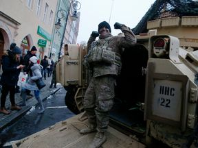 A US soldier flexes his muscles after an official welcoming ceremony in Zagan