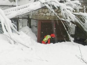 A member of Lazio's Alpine and Speleological Rescue Team is seen in front of the Hotel Rigopiano in Farindola, central Italy