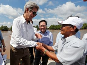 John Kerry shakes the hand of former Viet Cong soldier Vo Ban Tam